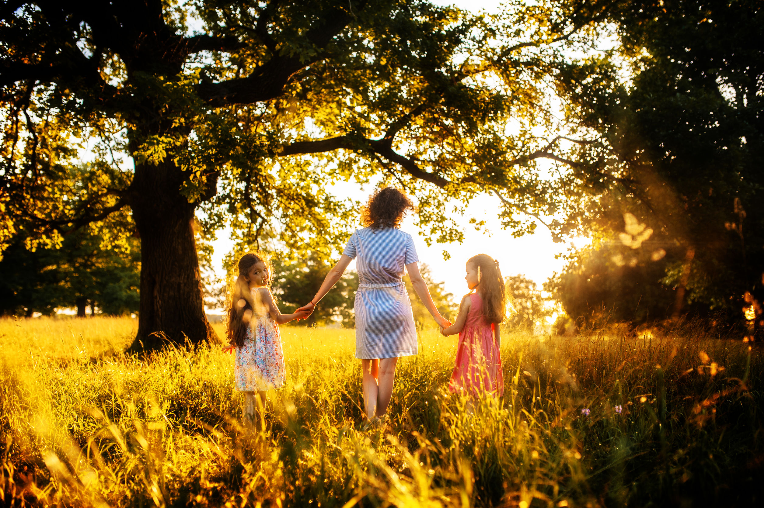 Mother and daughters hold hands on sunset in the forest