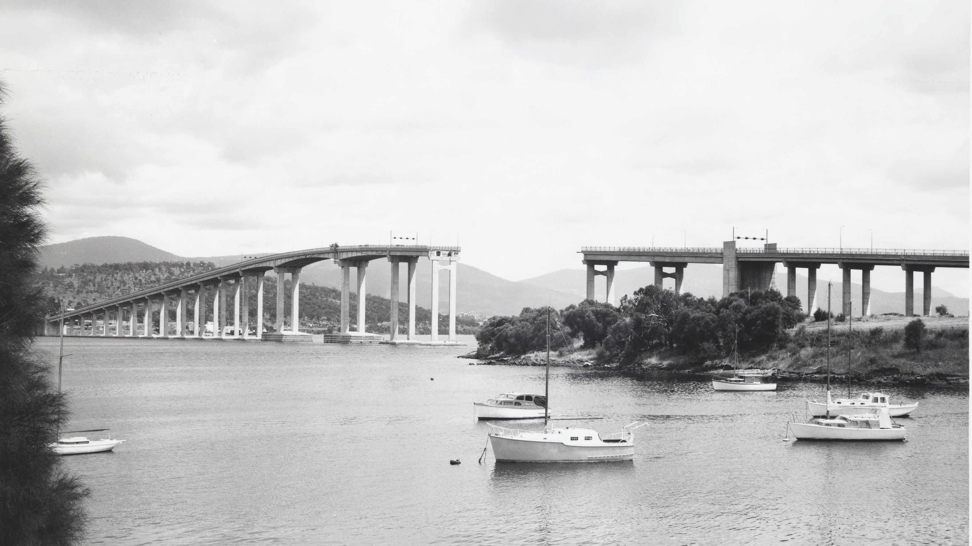 View_of_the_Tasman_Bridge_from_Kalatie_Road_Montague_Bay_looking_toward_the_Powder_Jetty_over_Cuthbertson's_Boat_shed_(1975)_(16200189861)